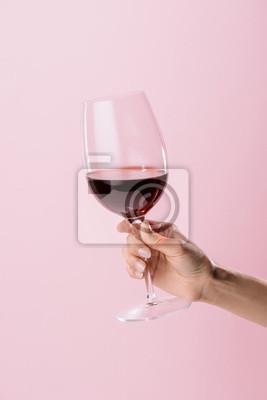 Fototapeta oříznutý záběr ženy držící sklenici červeného vína izolovaných na růžové
