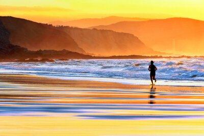 Fototapeta osoba, která provozuje na pláži při západu slunce