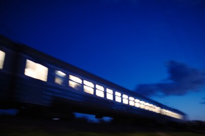 Fototapeta Osvětlený vlak cestování kolem v noci