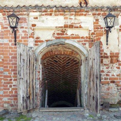Fototapeta Otevřené zvětralé dřevěné dveře vedoucí do jámy starého hradu