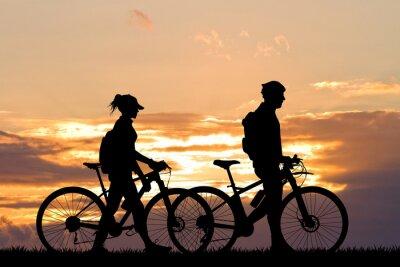 Fototapeta pár se na kole při západu slunce