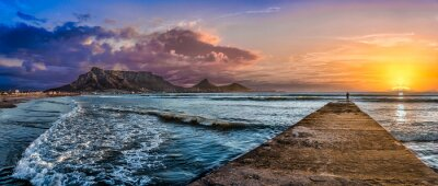 Fototapeta Picturesque and colourful sunset scene of Table Mountain and The Atlantic Ocean. A jetty reaches out to the cool blue sea to inspire a sense of adventure. A stunning tourist destination - Cape Town
