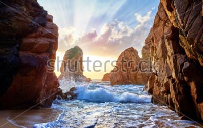 Fototapeta Písečná pláž mezi skalami na večerní slunce. Ursa Beach poblíž Cape Roca (Cabo da Roca) na pobřeží Atlantského oceánu v Portugalsku. Letní krajina.
