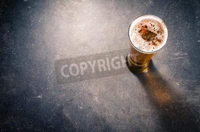 Fototapeta Pivní sklenice na tmavém stole