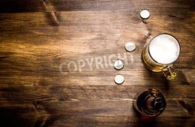 Fototapeta Pivo style- láhev, pivo ve skle a vztahuje se na dřevěném stole.
