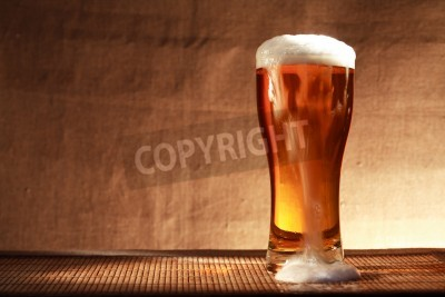 Fototapeta Plná sklenice svěžesti piva s pěnou na stole proti šedé plátně pozadí