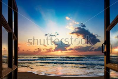 Fototapeta Pohled na východ slunce nad mořem z otevřeného okna
