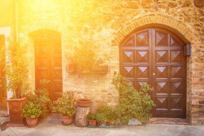 Fototapeta Pohled starobylého starého evropského města. Ulice Pienza, Itálie s dřevěnými dveřmi. Slunečné pozadí cestování.