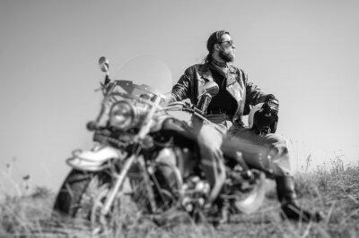 Fototapeta Portrét mladého muže s vousy seděl na křižník motocykl a při pohledu na slunce. Muž má na sobě koženou bundu a modré džíny. Nízký úhel pohledu. Tilt objektiv efekt rozostření. Černý a bílý