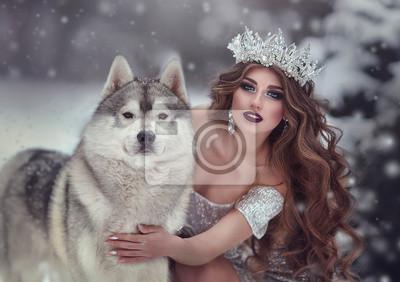 Fototapeta Portrét ženy ve stříbrných šatech a korunu jako sněhová královna, v zimním lese se psem Husky. Víla princezna a vlk v zimě.
