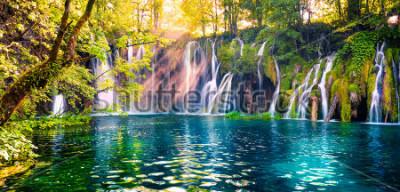 Fototapeta Poslední sluneční světlo na vodách v Národním parku Plitvice. Barevné jarní panorama zeleného lesa s modrým jezerem. Velký výhled na krajinu v Chorvatsku, v Evropě.