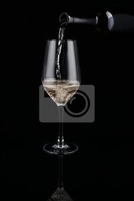Fototapeta Pouring of white wine from bottle into glass on dark background