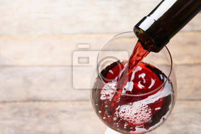 Fototapeta Pouring red wine from bottle into glass on blurred background, closeup. Space for text
