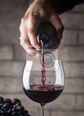 Fototapeta Pouring red wine into the glass against wooden background