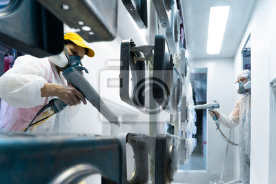 Fototapeta Powder coating of metal parts. Man and woman in protective suit sprays white powder paint from gun on metal products