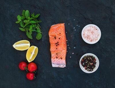 Fototapeta Přísady. Raw filet z lososa, citron, cherry rajčátka, čerstvá máta a koření přes tmavé kamenné pozadí