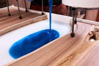 Fototapeta Process making of a craft resin and wood table. Liquid epoxy is poured into a mold with wooden blanks.