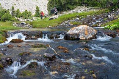 Fototapeta Rapid a široká řeka kaskáda Rychle se pohybující vody živé skalní kameny a skupinu lidí, kteří jdou na zelené louce na pozadí