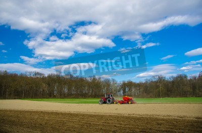 Fototapeta red tractor on an acre in spring