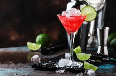 Fototapeta Red Watermelon alcoholic cocktail with vodka, juice, lime and crushed ice, metal bar tools, dark background