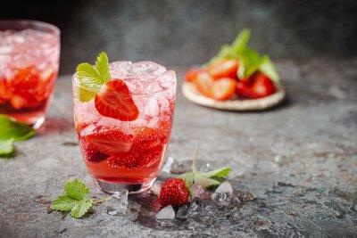 Fototapeta Refreshing summer drink with strawberry slices in glasses on dark background