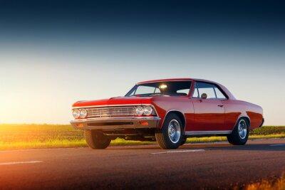 Fototapeta Retro červené auto pobyt na asfaltovou silnici při západu slunce