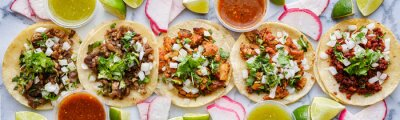 Fototapeta row of assorted mexican street tacos with garnishes in wide banner composition
