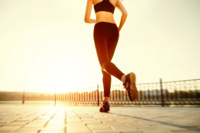 Fototapeta Runner feet running on road closeup on shoe. woman fitness sunri