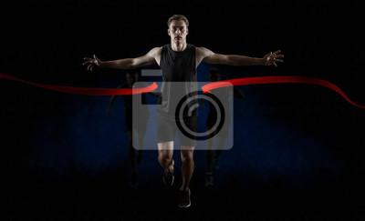 Fototapeta Runner wins by crossing the finish line on dark background