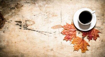 Fototapeta Šálek horké kávy s podzimní listí.