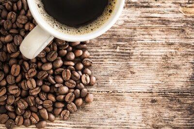 Fototapeta Šálek kávy a fazole na dřevěný stůl