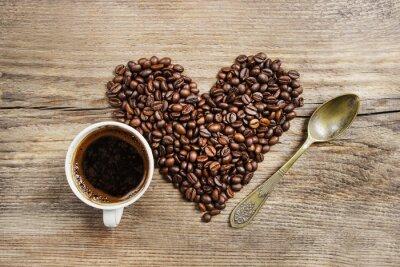 Fototapeta Šálek kávy a srdce z kávových zrn na dřevěném stole. Na