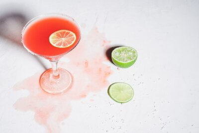 Fototapeta Salt rimmed Paloma cocktail  with tequila and grapefruit juice, lime slice garnish on white table, messy situation