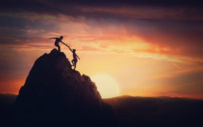 Fototapeta Scenery view with a team of two climbers on the top on the mountain. Person helping another to overcome obstacles and reach the top together. Teamwork concept, working in group to achieve success