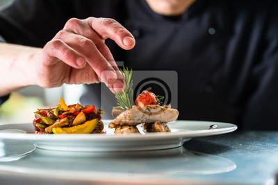 Fototapeta Šéfkuchař dokončil a zdobil jídlo, které připravil, misku s vepřovým masem a zeleninou