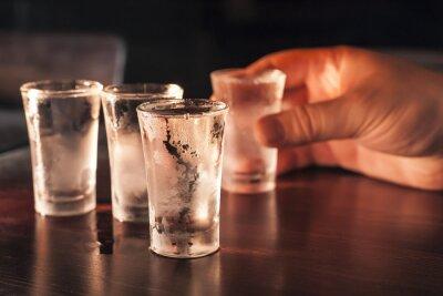 Fototapeta Shot sklenku vodky v ruce na dřevěný stůl.