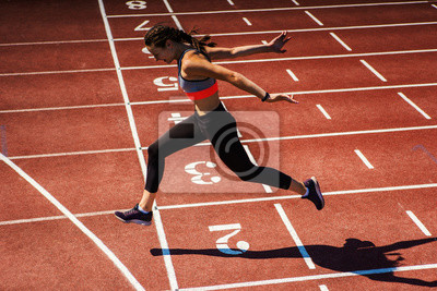 Fototapeta Side view of female teen athlete in sports bra and tights successfully finishing race on track at stadium