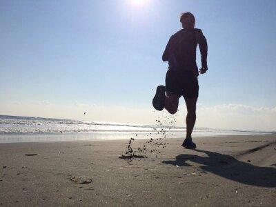 Fototapeta Silhoette člověka běží na pláži
