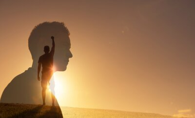 Fototapeta Silhouette of strong young man feeling determined, empowered and motivated putting fist up to the sky. People power and inner strength concept.