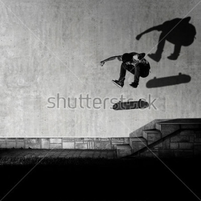 Fototapeta Skater making 360 flip trick from 4 stairs - artistic motion blur shot in black and white color tone.