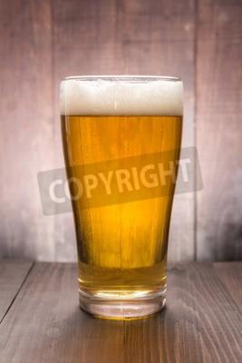 Fototapeta Sklenice piva na dřevěné pozadí.