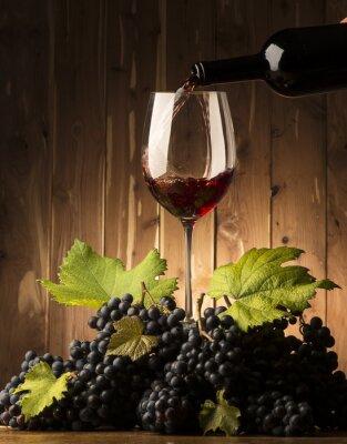 Fototapeta Sklo s červeným vínem a grapeson dřevěná tabulka