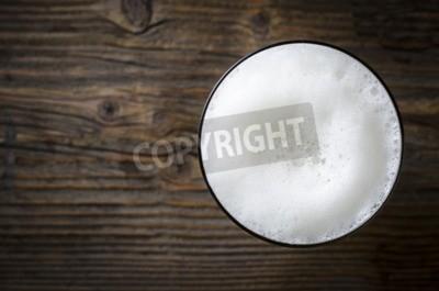 Fototapeta Sklo z pivní pěny přes dřevěný stůl