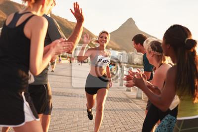 Fototapeta Skupina diváky jásajícím běžce na cílové čáře