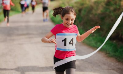 Fototapeta Small girl runner crossing finish line in a race competition in nature.