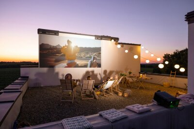 Fototapeta Small group of people watching movie on the rooftop terrace at sunset. Open air cinema concept. Romantic leisure and entertainment on the roof of a country house