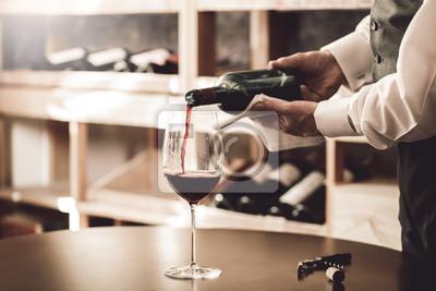 Fototapeta Sommelier Concept. Senior man standing pouring wine into glass elegant close-up