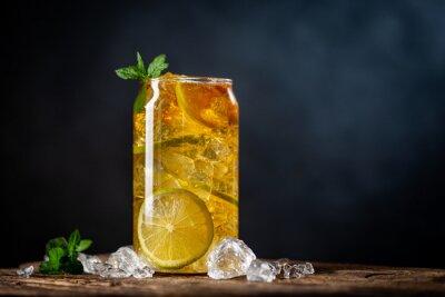 Fototapeta Summer drink Iced tea with lemon slices and mint on dark background
