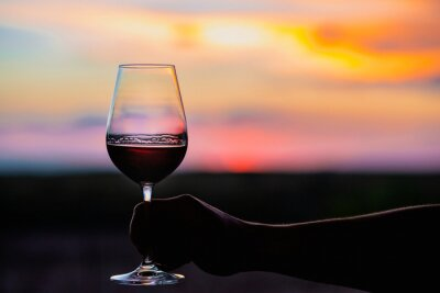 Fototapeta Sunset with a glass of wine.Beautiful sky with sunset with a glass of wine.A glass of wine at sunset in the mountains.Red wine. Relax.Summer concept.Summer with sunset.August. Summer vacation
