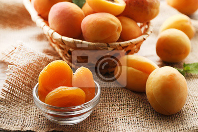 Fototapeta Sweet apricots in basket and bowl on sackcloth